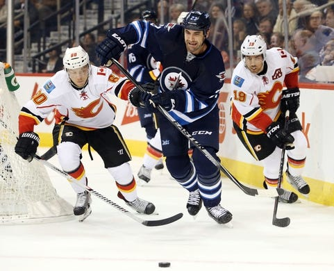 Oct 1, 2015; Winnipeg, Manitoba, CAN; Winnipeg Jets  defenceman  Adam Pardy (2) battles Calgary Flames center Markus Granlund (60) and Calgary Flames right wing David Jones (19) for the puck during the first period at MTS Centre. Mandatory Credit: Bruce Fedyck-USA TODAY Sports