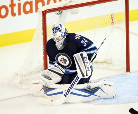 Oct 1, 2015; Winnipeg, Manitoba, CAN; Winnipeg Jets  goalie  Michael Hutchinson (34) makes a save during the second period against the Calgary Flames at MTS Centre. Mandatory Credit: Bruce Fedyck-USA TODAY Sports