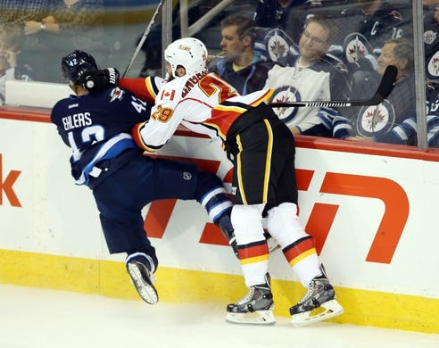 Oct 1, 2015; Winnipeg, Manitoba, CAN; Winnipeg Jets  forward  Nikolaj Ehlers (42) is taken into the boards by Calgary Flames defenseman Deryk Engelland (29) during the second at MTS Centre. Mandatory Credit: Bruce Fedyck-USA TODAY Sports
