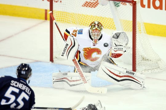 Oct 1, 2015; Winnipeg, Manitoba, CAN; Winnipeg Jets  forward  Mark Scheifele (55) takes a shot on Calgary Flames goalie Joni Ortio (37) during the second at MTS Centre. Mandatory Credit: Bruce Fedyck-USA TODAY Sports