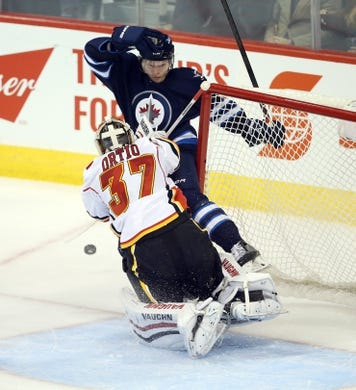 Oct 1, 2015; Winnipeg, Manitoba, CAN; Winnipeg Jets  defenceman  Jacob Trouba (8) collides with Calgary Flames goalie Joni Ortio (37) during the second at MTS Centre. Mandatory Credit: Bruce Fedyck-USA TODAY Sports