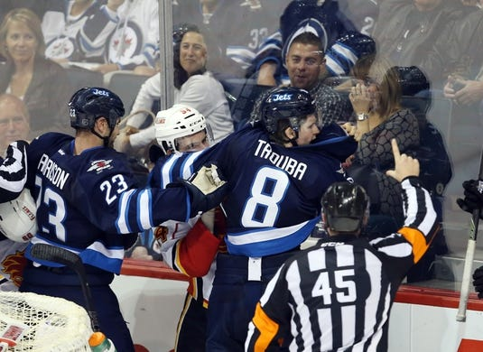 Oct 1, 2015; Winnipeg, Manitoba, CAN; Winnipeg Jets  defenceman  Jacob Trouba fights with Calgary Flames right wing Garnet Hathaway (64) during the second at MTS Centre. Mandatory Credit: Bruce Fedyck-USA TODAY Sports