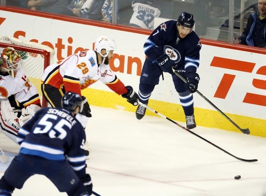 Oct 1, 2015; Winnipeg, Manitoba, CAN; Winnipeg Jets  defenceman  Ben Chariot (7) looks to make a pass to Winnipeg Jets  forward  Mark Scheifele (55) during second period at MTS Centre. Mandatory Credit: Bruce Fedyck-USA TODAY Sports