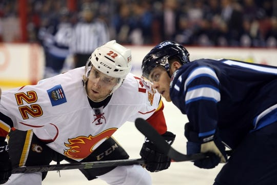 Oct 1, 2015; Winnipeg, Manitoba, CAN; Winnipeg Jets  forward  Adam Lowry (17) takes the draw against Calgary Flames center Drew Shore (22) during the third period at MTS Centre. Winnipeg wins 3-1. Mandatory Credit: Bruce Fedyck-USA TODAY Sports