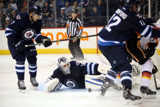 Oct 1, 2015; Winnipeg, Manitoba, CAN; Winnipeg Jets  goalie  Michael Hutchinson (34) makes a save during the third period against the Calgary Flames at MTS Centre. Winnipeg wins 3-1. Mandatory Credit: Bruce Fedyck-USA TODAY Sports