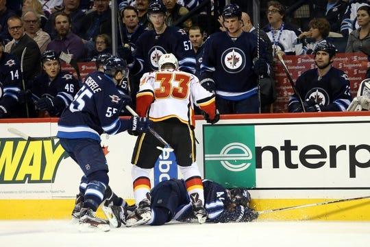 Oct 1, 2015; Winnipeg, Manitoba, CAN; Winnipeg Jets  forward  Nikolaj Ehlers (42) is hit into the boards by Calgary Flames defenseman Jakub Nakladal (33) during the third period at MTS Centre. Winnipeg wins 3-1. Mandatory Credit: Bruce Fedyck-USA TODAY Sports