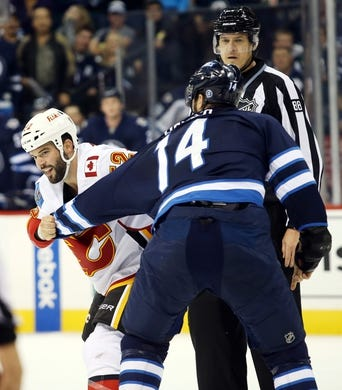 Oct 1, 2015; Winnipeg, Manitoba, CAN; Winnipeg Jets  forward  Anthony Peluso (14) fights Calgary Flames left wing Brandon Bollig (52) during the third period at MTS Centre. Winnipeg wins 3-1. Mandatory Credit: Bruce Fedyck-USA TODAY Sports