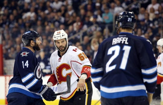 Oct 1, 2015; Winnipeg, Manitoba, CAN; Winnipeg Jets  forward  Thomas Raffl (21) is challenged by Calgary Flames left wing Brandon Bollig (52) then confronted by Winnipeg Jets  forward  Anthony Peluso (14) during the third period at MTS Centre. Winnipeg wins 3-1. Mandatory Credit: Bruce Fedyck-USA TODAY Sports