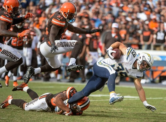Oct 4, 2015; San Diego, CA, USA; San Diego Chargers running back Danny Woodhead (39) tries to high step out of a tackle by Cleveland Browns cornerback Jordan Poyer (33) for a 19-yard gain in the closing minute of the fourth quarter at Qualcomm Stadium. The Chargers went on to a 30-27 win.  Cleveland strong safety Donte Whitner (31) and inside linebacker Chris Kirksey (58) trail the play at left. Mandatory Credit: Robert Hanashiro-USA TODAY Sports
