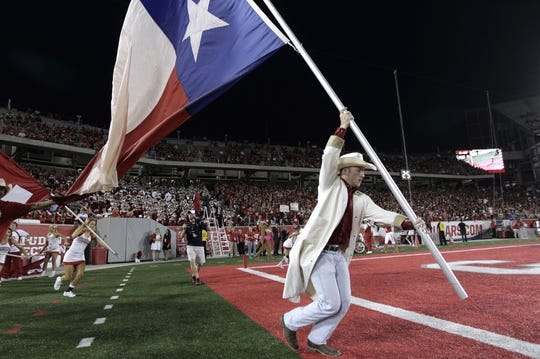 Oct 8, 2015; Houston, TX, USA; A University of Houston Cougars Frontiersman runs with the Texas state flag after a Cougar touchdown against the Southern Methodist University Mustangs at TDECU Stadium. Mandatory Credit: Erich Schlegel-USA TODAY Sports
