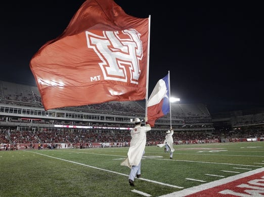 Oct 8, 2015; Houston, TX, USA; University of Houston Cougars Frontiersmen run with the Texas state flag and the U of H flag after a Cougar touchdown against the Southern Methodist University Mustangs at TDECU Stadium. Mandatory Credit: Erich Schlegel-USA TODAY Sports