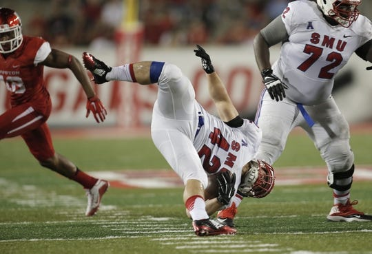 Oct 8, 2015; Houston, TX, USA; Southern Methodist University Mustangs running back Prescott Line (42) gets upended by a University of Houston Cougars defender in the second half at TDECU Stadium. Mandatory Credit: Erich Schlegel-USA TODAY Sports