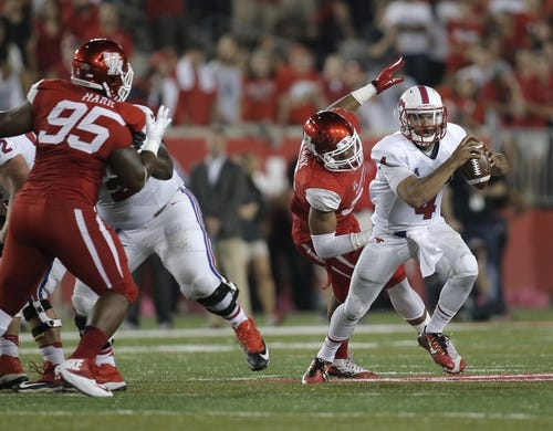Oct 8, 2015; Houston, TX, USA; Southern Methodist University Mustangs quarterback Matt Davis (4) scrambles away from University of Houston Cougars defenders in the second half at TDECU Stadium. Mandatory Credit: Erich Schlegel-USA TODAY Sports