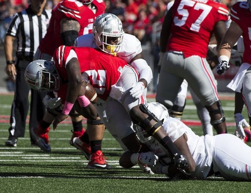 Oct 10, 2015; Columbus, OH, USA;Ohio State Buckeyes quarterback Cardale Jones (12) is sacked by Maryland Terrapins defensive linemen Yannick Ngakoue (7) and Azubuike Ukandu (95) at Ohio Stadium. Mandatory Credit: Greg Bartram-USA TODAY Sports