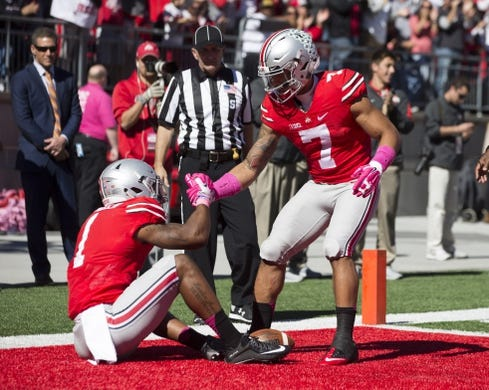 Oct 10, 2015; Columbus, OH, USA; Ohio State Buckeyes wide receiver Braxton Miller (1) is helped to his feet by a teammate after his touchdown against the Maryland Terrapins at Ohio Stadium. Mandatory Credit: Greg Bartram-USA TODAY Sports