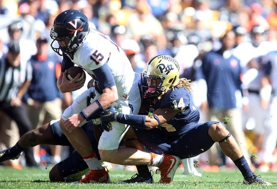 Oct 10, 2015; Pittsburgh, PA, USA; Virginia Cavaliers quarterback Matt Johns (15) is sacked by Pittsburgh Panthers defensive lineman Ejuan Price (left) and defensive back Avonte Maddox (14) during the second quarter at Heinz Field. Mandatory Credit: Charles LeClaire-USA TODAY Sports
