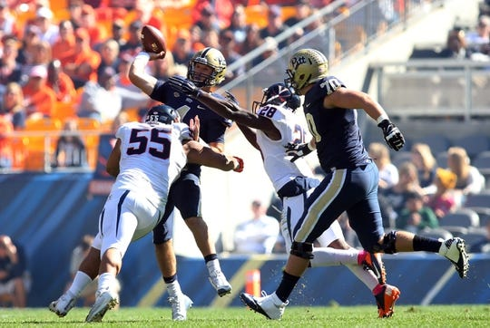 Oct 10, 2015; Pittsburgh, PA, USA; Pittsburgh Panthers quarterback Nathan Peterman (4) passes under pressure from Virginia Cavaliers defensive tackle David Dean (55) and safety Wilfred Wahee (28) during the second quarter at Heinz Field. Mandatory Credit: Charles LeClaire-USA TODAY Sports
