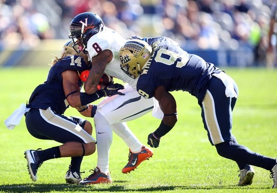 Oct 10, 2015; Pittsburgh, PA, USA; Virginia Cavaliers wide receiver T.J. Thorpe (8) is tackled after a catch by Pittsburgh Panthers defensive back Avonte Maddox (14) and defensive back Jordan Whitehead (9) during the third quarter at Heinz Field. PITT won 26-19. Mandatory Credit: Charles LeClaire-USA TODAY Sports