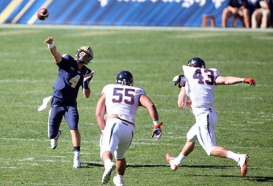 Oct 10, 2015; Pittsburgh, PA, USA; Pittsburgh Panthers quarterback Nathan Peterman (4) passes over Virginia Cavaliers defensive tackle David Dean (55) and defensive end Trent Corney (43) during the third quarter at Heinz Field. PITT won 26-19. Mandatory Credit: Charles LeClaire-USA TODAY Sports