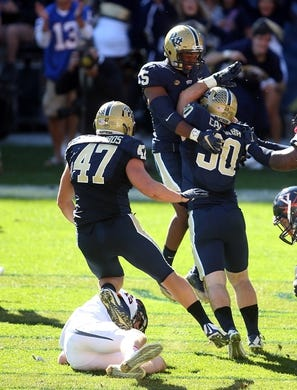 Oct 10, 2015; Pittsburgh, PA, USA; Pittsburgh Panthers linebacker Matt Galambos (47) and defensive back Reggie Mitchell (15) congratulate linebacker Mike Caprara (30) after Caprara sacked Virginia Cavaliers quarterback Matt Johns (bottom) in the end-zone for a safety during the fourth quarter at Heinz Field. PITT won 26-19. Mandatory Credit: Charles LeClaire-USA TODAY Sports