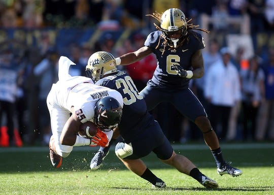Oct 10, 2015; Pittsburgh, PA, USA; Pittsburgh Panthers linebacker Mike Caprara (30) and defensive back Lafayette Pitts (6) defend as Virginia Cavaliers wide receiver Keeon Johnson (85) makes a catch during the fourth quarter at Heinz Field. PITT won 26-19. Mandatory Credit: Charles LeClaire-USA TODAY Sports