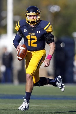Oct 10, 2015; Toledo, OH, USA; Toledo Rockets quarterback Phillip Ely (12) rolls out to his right during the second quarter against the Kent State Golden Flashes at Glass Bowl. Mandatory Credit: Raj Mehta-USA TODAY Sports