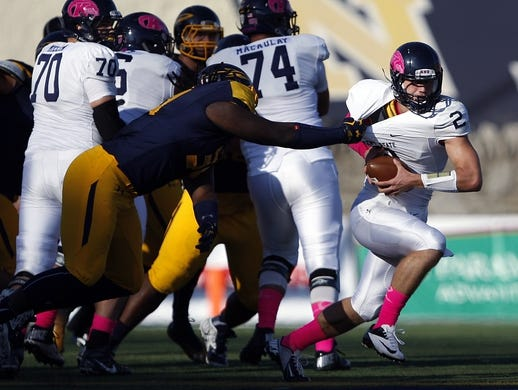 Oct 10, 2015; Toledo, OH, USA; Kent State Golden Flashes quarterback George Bollas (2) grabbed by Toledo Rockets defensive end Keenen Gibbs (34) during the second quarter at Glass Bowl. Mandatory Credit: Raj Mehta-USA TODAY Sports