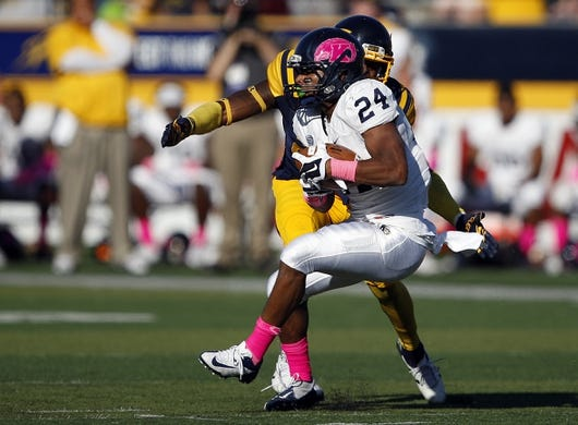 Oct 10, 2015; Toledo, OH, USA; Kent State Golden Flashes running back Raekwon James (24) defended by Toledo Rockets defensive back DeJuan Rogers (23) during the second quarter at Glass Bowl. Mandatory Credit: Raj Mehta-USA TODAY Sports