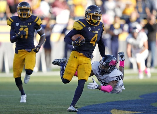 Oct 10, 2015; Toledo, OH, USA; Kent State Golden Flashes linebacker Dustyn Moore (30) tries to tackle Toledo Rockets wide receiver Corey Jones (4) during the fourth quarter at Glass Bowl. Rockets win 38-7. Mandatory Credit: Raj Mehta-USA TODAY Sports