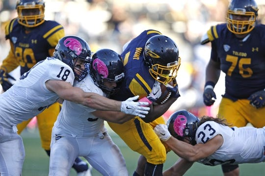 Oct 10, 2015; Toledo, OH, USA; Toledo Rockets running back Kareem Hunt (3) gets tackled by a group of Kent State Golden Flashes during the fourth quarter at Glass Bowl. Rockets win 38-7. Mandatory Credit: Raj Mehta-USA TODAY Sports
