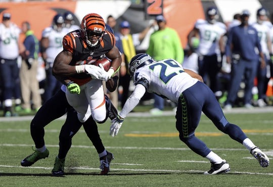 Oct 11, 2015; Cincinnati, OH, USA; Cincinnati Bengals wide receiver Mohamed Sanu (12) makes a catch and is tackled by Seattle Seahawks free safety Earl Thomas (29) in the second half at Paul Brown Stadium. The Bengals won 27-24. Mandatory Credit: Aaron Doster-USA TODAY Sports