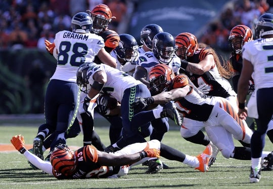 Oct 11, 2015; Cincinnati, OH, USA; Seattle Seahawks running back Thomas Rawls (34) carries the ball as he is tackled by Cincinnati Bengals defensive tackle Geno Atkins (97) in the second half at Paul Brown Stadium. The Bengals won 27-24. Mandatory Credit: Aaron Doster-USA TODAY Sports