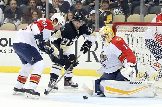 Oct 20, 2015; Pittsburgh, PA, USA; Florida Panthers goalie Roberto Luongo (1) makes a save against Pittsburgh Penguins right wing Bryan Rust (17) as defenseman Brian Campbell (51) depends during the first period at the CONSOL Energy Center. Mandatory Credit: Charles LeClaire-USA TODAY Sports