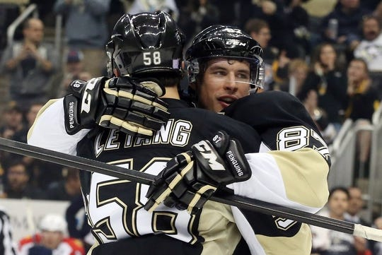 Oct 20, 2015; Pittsburgh, PA, USA; Pittsburgh Penguins center Sidney Crosby (87) celebrates his goal with defenseman Kris Letang (58) against the Florida Panthers during the first period at the CONSOL Energy Center. Mandatory Credit: Charles LeClaire-USA TODAY Sports
