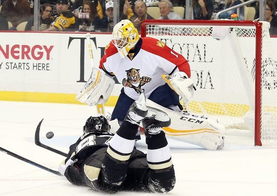 Oct 20, 2015; Pittsburgh, PA, USA; Pittsburgh Penguins center Sidney Crosby (87) shoots the puck while prone as Florida Panthers goalie Roberto Luongo (1) makes a save during the first period at the CONSOL Energy Center. Mandatory Credit: Charles LeClaire-USA TODAY Sports