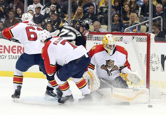 Oct 20, 2015; Pittsburgh, PA, USA; Florida Panthers goalie Roberto Luongo (1) makes a save against Pittsburgh Penguins right wing Patric Hornqvist (72) as Panthers center Dave Bolland (63) and defenseman Dmitry Kulikov (7) defend during the first period at the CONSOL Energy Center. Mandatory Credit: Charles LeClaire-USA TODAY Sports