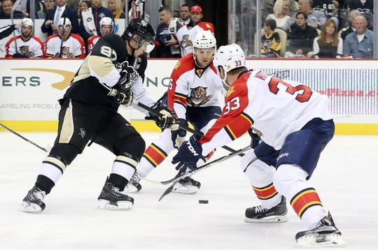 Oct 20, 2015; Pittsburgh, PA, USA; Pittsburgh Penguins center Sidney Crosby (87) chases the puck as Florida Panthers defenseman Alex Petrovic (6) and defenseman Willie Mitchell (33) defend during the third period at the CONSOL Energy Center. The Penguins won 3-2 in overtime. Mandatory Credit: Charles LeClaire-USA TODAY Sports