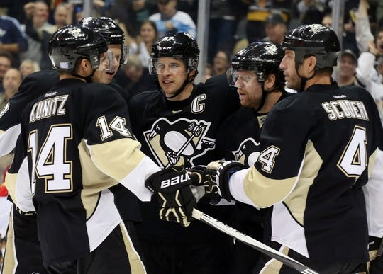 Oct 20, 2015; Pittsburgh, PA, USA; Pittsburgh Penguins left wing Chris Kunitz (14) and defenseman Olli Maatta (LC) and center Sidney Crosby (C) and defenseman Rob Scuderi (4) celebrate a goal by Penguins right wing Phil Kessel (RC) against the Florida Panthers during the third period at the CONSOL Energy Center. The Penguins won 3-2 in overtime. Mandatory Credit: Charles LeClaire-USA TODAY Sports