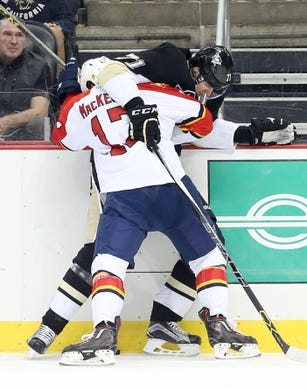 Oct 20, 2015; Pittsburgh, PA, USA; Florida Panthers center Derek MacKenzie (17) and Pittsburgh Penguins center Evgeni Malkin (71) battle for the puck along the boards during the third period at the CONSOL Energy Center. The Penguins won 3-2 in overtime. Mandatory Credit: Charles LeClaire-USA TODAY Sports