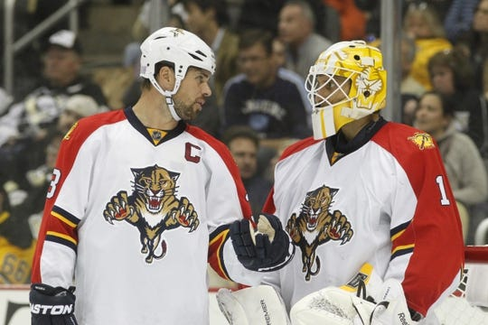 Oct 20, 2015; Pittsburgh, PA, USA; Florida Panthers defenseman Willie Mitchell (33) and goalie Roberto Luongo (1) talk during a goal review against the Pittsburgh Penguins during the third period at the CONSOL Energy Center. The Penguins won 3-2 in overtime. Mandatory Credit: Charles LeClaire-USA TODAY Sports