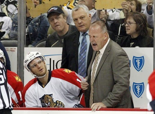 Oct 20, 2015; Pittsburgh, PA, USA; Florida Panthers head coach Gerard Gallant (right) reacts on the bench as center Jonathan Huberdeau (11) and assistant coach Mike Kelly (rear) look on against the Pittsburgh Penguins during the third period at the CONSOL Energy Center. The Penguins won 3-2 in overtime. Mandatory Credit: Charles LeClaire-USA TODAY Sports
