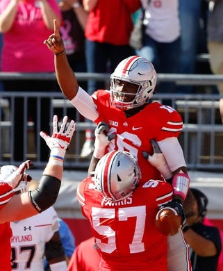 Oct 10, 2015; Columbus, OH, USA; Ohio State Buckeyes quarterback J.T. Barrett (16) is hoisted up by teammate Chase Farris (57) following his second half touchdown versus the Maryland Terrapins at Ohio Stadium. Ohio State won the game 49-28. Mandatory Credit: Joe Maiorana-USA TODAY Sports