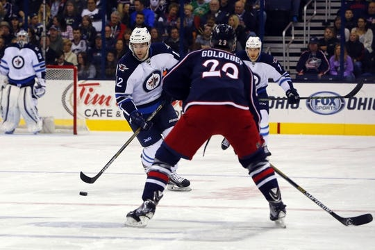Oct 31, 2015; Columbus, OH, USA; Winnipeg Jets right wing Drew Stafford (12) controls the puck as Columbus Blue Jackets defenseman Cody Goloubef (29) defends during the first period at Nationwide Arena. Mandatory Credit: Russell LaBounty-USA TODAY Sports