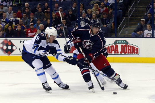 Oct 31, 2015; Columbus, OH, USA; Winnipeg Jets center Andrew Copp (9) steals the puck from Columbus Blue Jackets left wing Brandon Saad (20) during the second period at Nationwide Arena. Mandatory Credit: Russell LaBounty-USA TODAY Sports
