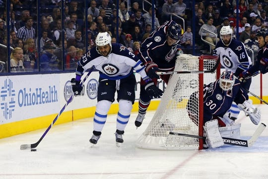 Oct 31, 2015; Columbus, OH, USA; Winnipeg Jets defenseman Dustin Byfuglien (33) controls the puck as Columbus Blue Jackets defenseman Kevin Connauton (4) trails the play during the third period at Nationwide Arena. Winnipeg defeated Columbus 3-2. Mandatory Credit: Russell LaBounty-USA TODAY Sports