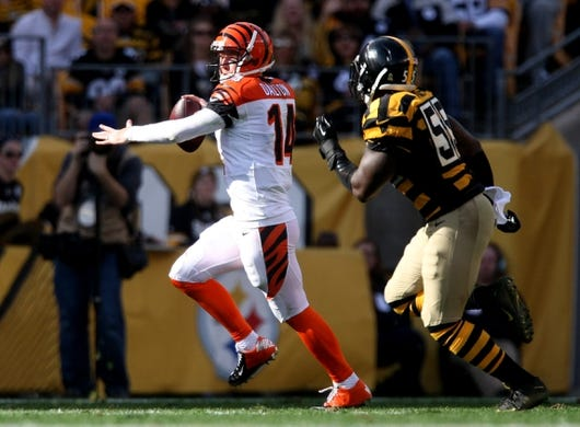 Nov 1, 2015; Pittsburgh, PA, USA; Cincinnati Bengals quarterback Andy Dalton (14) looks to throw as he is chased by Pittsburgh Steelers linebacker Arthur Moats (55) during the first half at Heinz Field. Mandatory Credit: Jason Bridge-USA TODAY Sports