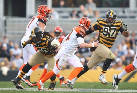 Nov 1, 2015; Pittsburgh, PA, USA; Cincinnati Bengals quarterback Andy Dalton (14) scrambles against pressure from Pittsburgh Steelers nose tackle Steve McLendon (90) and defensive end Cameron Heyward (97) during the third quarter at Heinz Field. The Bengals won 16-10. Mandatory Credit: Charles LeClaire-USA TODAY Sports