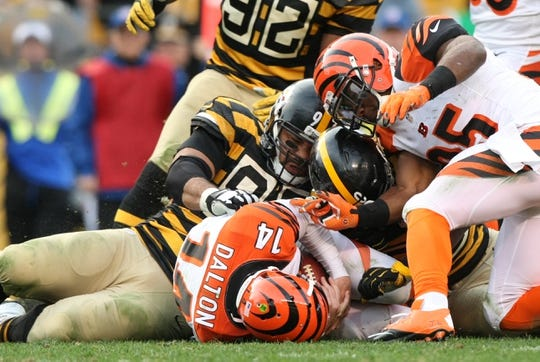 Nov 1, 2015; Pittsburgh, PA, USA; Cincinnati Bengals quarterback Andy Dalton (14) is sacked by Pittsburgh Steelers defensive end Cameron Heyward (97) and linebacker Ryan Shazier (50) during the second half at Heinz Field. The Bengals won the game 16-10. Mandatory Credit: Jason Bridge-USA TODAY Sports