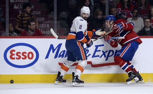 Nov 5, 2015; Montreal, Quebec, CAN; Montreal Canadiens forward Dale Weise (22) pushes the puck past New York Islanders defenseman Nick Leddy (2) during the first period at the Bell Centre. Mandatory Credit: Eric Bolte-USA TODAY Sports