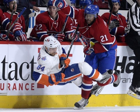 Nov 5, 2015; Montreal, Quebec, CAN; Montreal Canadiens forward Devante Smith-Pelly (21) collides with New York Islanders forward Mikhail Grabovski (84) during the first period at the Bell Centre. Mandatory Credit: Eric Bolte-USA TODAY Sports